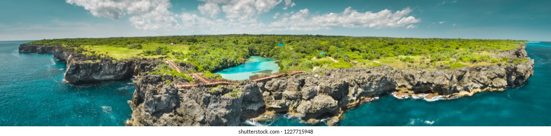 Aerial drone shot green-capped island, ocean. Panorama. Indonesia. Spectacular view from above Sumba island the plain with greens and pure lakes on the blue cloudy sky background. Indian ocean.