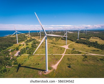 Aerial drone shot of huge electricity windmills in the green field near the sea