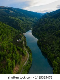Aerial drone shot of a lake and green forest in Transylvania, Romania