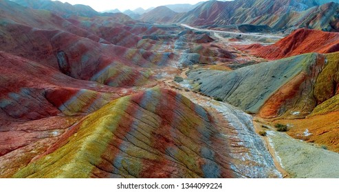 Aerial drone shot of most colorful landscape on earth, the rainbow mountains of Zhangye Danxia National Geological Park. Breath-taking multicolored slopes covered by striped pattern.