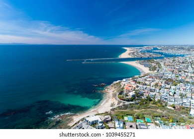 Aerial drone shot over Newport Beach in Orange County, California with coastal homes, blue skies, beaches and harbor entrance in view.