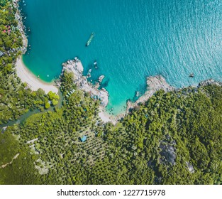 Aerial drone shot overview ocean, beach, forest. Bali. Amazing panoramic view from above Indian ocean, white sand beach and dense greens. Beauty of wild virgin Indonesian nature.