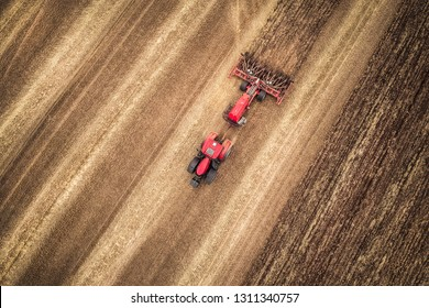 Aerial drone shot of red tractor seeding after the harvest in South Moravia, Czech Republic. Precision GPS agriculture stubble-tillage in the field from the top.
