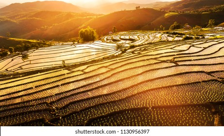 Aerial drone shot of sunset at Terraced Paddy Field in Mae-Jam Village , Chaing mai Province , Thailand. Top view Pa Pong Piang rice field.