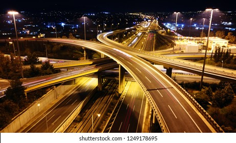 Aerial drone slow shutter night shot of urban elevated toll road junction and interchange overpass in rush hour