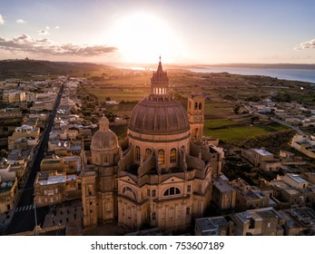 Aerial drone sunrise photo - Rotunda St. John Baptist Church in the town of Xewkija, Gozo.  Country of Malta.  Mediterranean Sea on the horizon