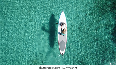 Aerial drone top down photo of fit unidentified woman paddling on a SUP board or Stand Up Paddle board in tropical exotic turquoise clear sea
