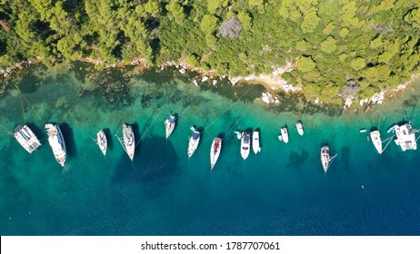 Aerial drone top down photo of safe small fjord harbour near bay of Panormos a popular yacht and sail boat anchorage with calm sea covered with pine trees, Skopelos island, Sporades, Greece