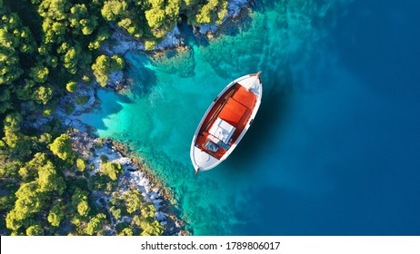 Aerial drone top down photo of traditional fishing boat anchored near small picturesque port of Agnontas, Skopelos, Sporades, Greece