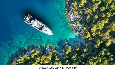 Aerial drone top down photo of inflatable speed boat anchored in tropical exotic island covered with pine trees - Shutterstock ID 1790004689