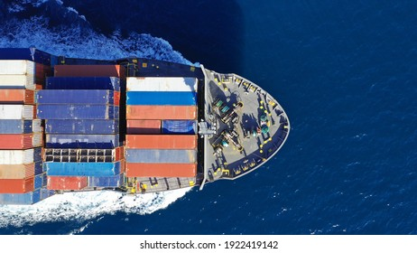 Aerial drone top down photo of colourful truck size container tanker ship cruising Mediterranean deep blue sea