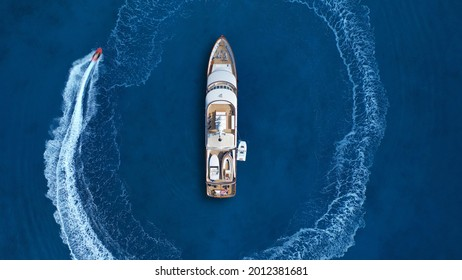 Aerial drone top down photo of stunt man performing extreme stunts and circling with jet ski watercraft over anchored yacht in deep blue ocean sea