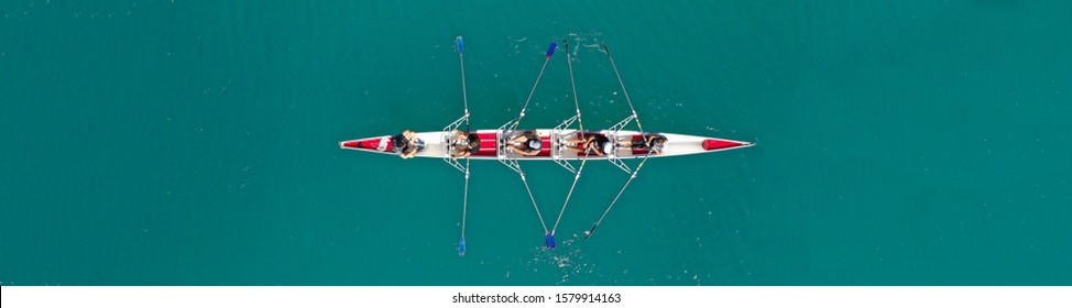 Aerial drone top down ultra wide panoramic view of sport canoe rowing synchronous athletes competing in tropical exotic lake