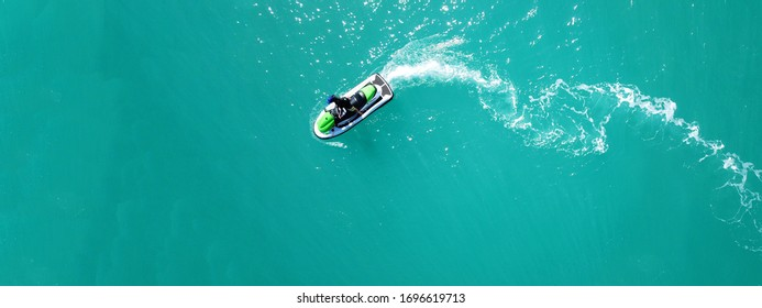 Aerial drone top down ultra wide photo of jet ski watercraft cruising in low speed in tropical exotic lake with calm emerald waters