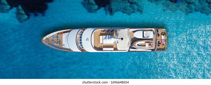 Aerial drone top down ultra wide photo of luxury yacht anchored in tropical exotic island bay with crystal clear turquoise sea