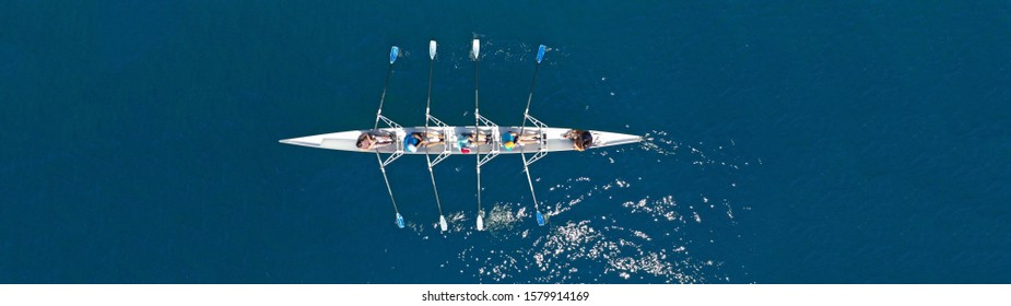 Aerial drone top ultra wide panoramic view of sport canoe rowing synchronous athletes competing in tropical exotic lake