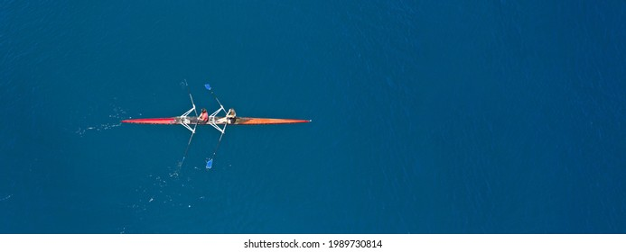 Lufttrockner auf der Spitze ultra breit Panoramasicht auf sportliche Kanurudersynchron männliche Athleten, die in tiefblauem Meer konkurrieren