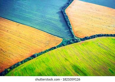 Lufttrockner-Top-Aussichtsfelder von Raps, Weizen und Soja mit Linien von Traktorstrecken auf sonnigen Frühling oder Sommertag. Naturhintergrund, Landschaftsfotografie