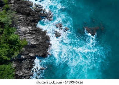 Aerial drone top view of ocean's beautiful waves crashing on the rocky island coast