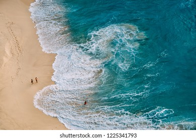 Aerial drone top view on ocean beach landscape with turquoise water, strong waves and yellow sand. Nusa Penida island, Bali, Indonesia. People walking, swimming, having fun. Travel Nature Background