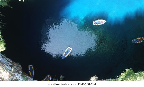 Aerial drone top view photo of iconic open cave and lake of Melissani near port of Sami, Cefalonia island, Ionian, Greece