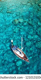 Aerial drone top view photo of sail boat with wooden deck docked in tropical caribbean paradise bay with white rock caves and turquoise clear sea