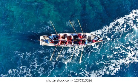 Aerial drone top view photo of crew rowing in traditional wooden vessel
