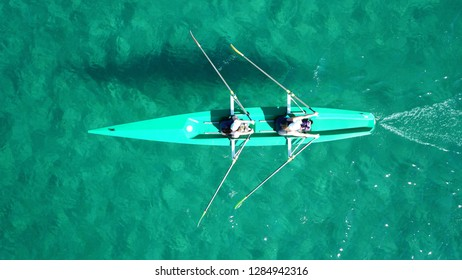 Aerial drone top view photo of 2 women practising sport canoe in tropical exotic emerald shalow waters