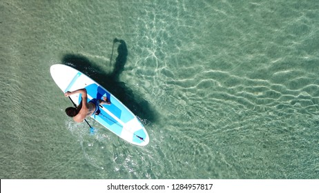 Aerial drone top view photo of men practising Stand Up Paddle or SUP board in mediterranean clear Aegean island sea