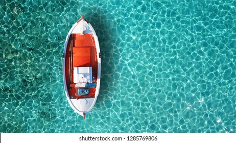 Aerial drone top view photo of red wooden traditional fishing boat in turquoise sea shore of Mykonos island, Cyclades, Greece
