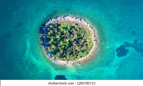 Aerial drone top view photo of small exotic atoll island with deep turquoise and emerald open ocean sea
