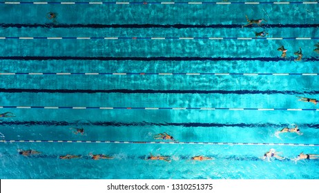 Aerial drone top view photo of open outdoor deep turquoise pool with swimmers practising