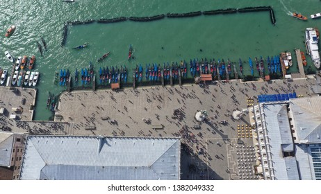 Aerial drone top view photo of colourful Gondolas docked in front of Doge's Palace in Saint Mark's square in the heart of Venice, Italy