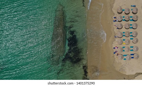 Aerial drone top view photo of breathtaking turquoise sandy beach of Plaka with sun beds and umbrellas, Naxos island, Cyclades, Greece