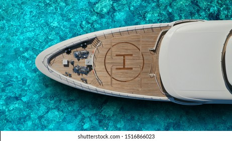 Aerial drone top view photo of large yacht - boat with helicopter landing area anchored in tropical exotic paradise with turquoise open sea