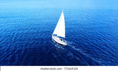 Aerial drone top view photo of sail boat sailing in mediterranean Aegean island of Santorini, Cyclades, Greece