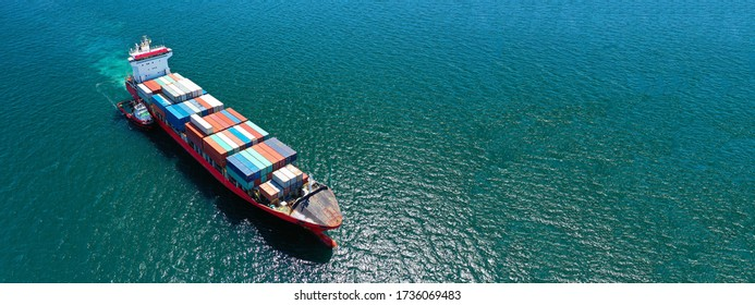 Aerial drone ultra wide panoramic photo of huge cargo ship carrying huge colourful truck size containers cruising deep blue sea