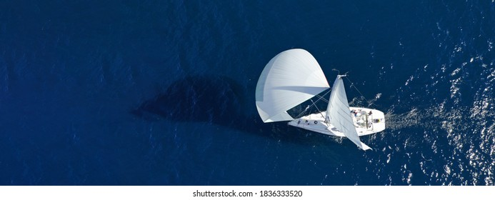 Aerial drone ultra wide panoramic photo of beautiful sail boat with white sails cruising deep blue sea near Mediterranean destination port