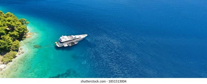 Lufttrockone ultra breites Panoramabild von Luxus-Yacht verankert in tropischen exotischen Insel mit kristallklares türkisblaues Meer und Pinien-Bäume
