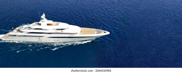 Aerial drone ultra wide panoramic photo of beautiful modern super yacht with wooden deck cruising in high speed deep blue open ocean sea