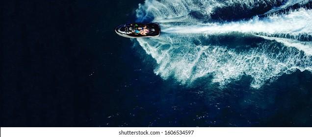 Aerial drone ultra wide photo of jet ski watercraft cruising in high speed in deep blue open ocean sea