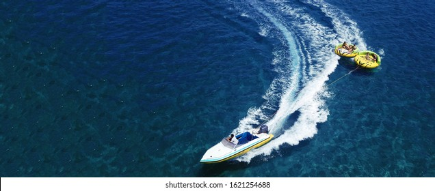 Aerial drone ultra wide photo of extreme powerboat donut water-sports cruising in high speed in tropical turquoise bay