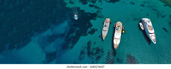 Aerial drone ultra wide photo of yachts anchored in famous beach of Super Paradise with turquoise clear sea, Mykonos island, Cyclades, Greece
