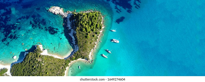 Aerial drone ultra wide photo of paradise turquoise bay and small village of Lakka visited by yachts and sail boats, Paxos island, Ionian, Greece