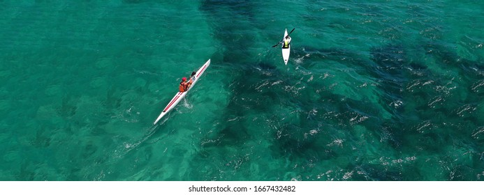 Aerial drone ultra wide photo of fit men competing in sport canoe in tropical exotic bay with emerald sea