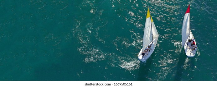 Aerial drone ultra wide photo of sail boats competing in annual regatta race in Saronic gulf, Greece