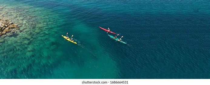 Aerial drone ultra wide photo of young couple canoeing in tropical exotic island bay