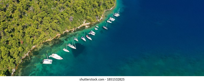 Aerial drone ultra wide photo of safe small fjord harbour of Mplo near bay of Panormos a popular yacht and sailboat anchorage with calm sea covered with pine trees, Skopelos island, Sporades, Greece