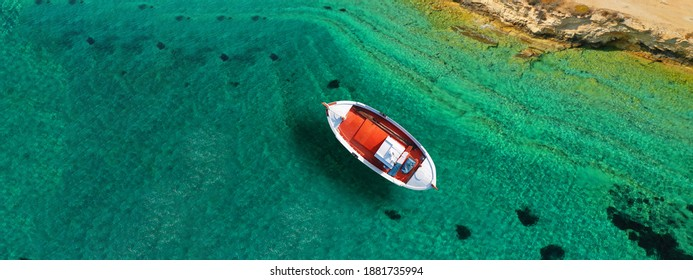 Aerial drone ultra wide photo of traditional fishing boat cruising in small Cycladic island of Schinoussa, Aegean Sea, Greece