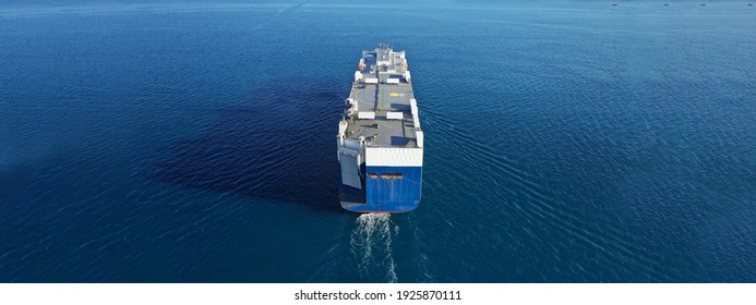 Aerial drone ultra wide photo of huge car carrier ship RO-RO (Roll on Roll off) cruising in Mediterranean deep blue Aegean sea